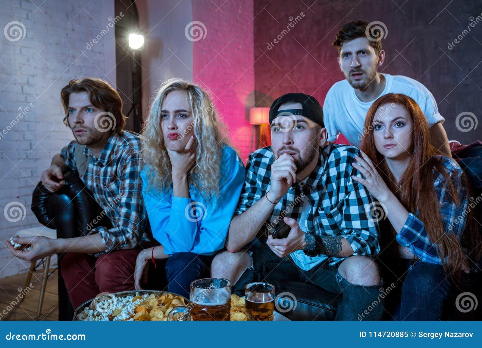 Grupo De Amigos Que Ven La Tv Hacer Juego En Casa Imagen De Archivo