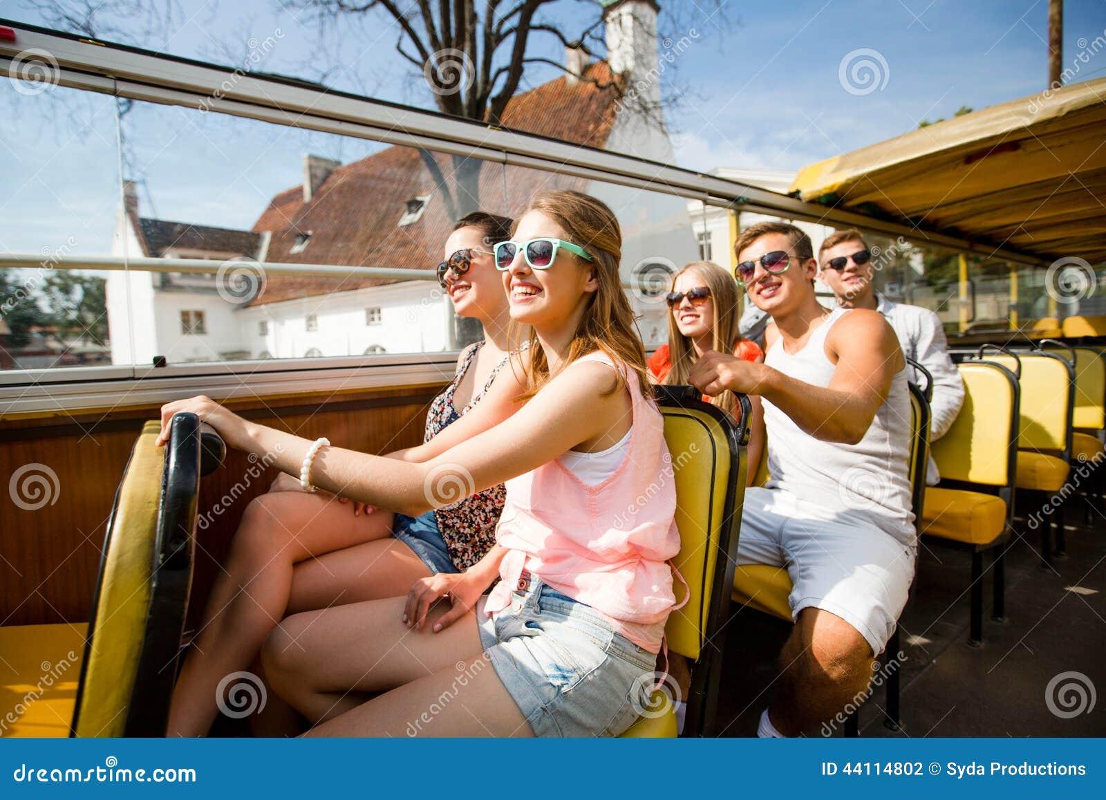 Grupo de amigos sonrientes que viajan en bus turístico