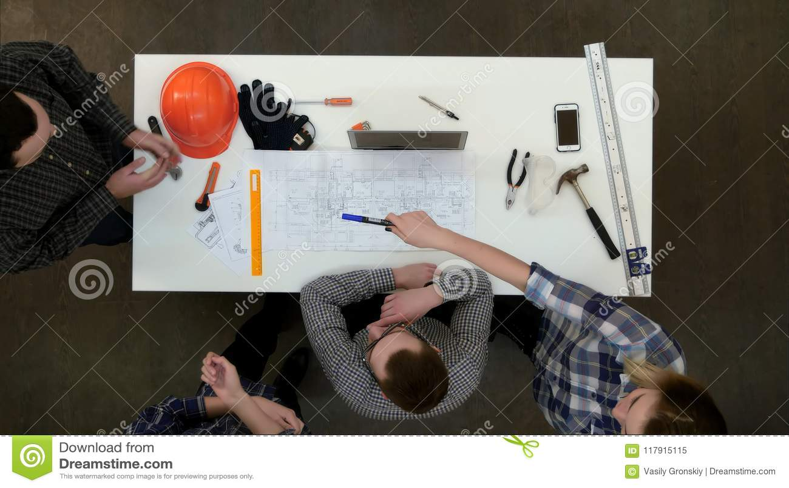 Grupo de arquitectos jovenes que trabajan en dibujos y que hacen medidas con la regla y el divisor