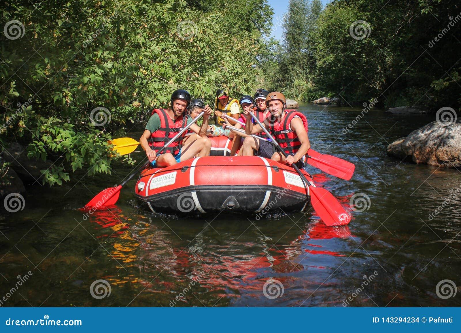 Grupo de aventurero que goza que transporta el río en balsa