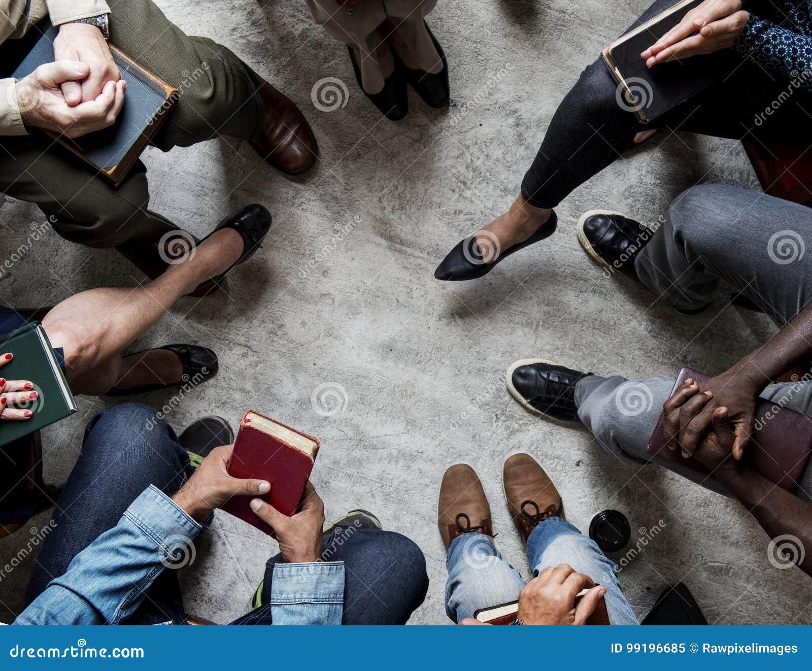 Grupo de biblia de la lectura de la gente del cristianismo que se sienta junto