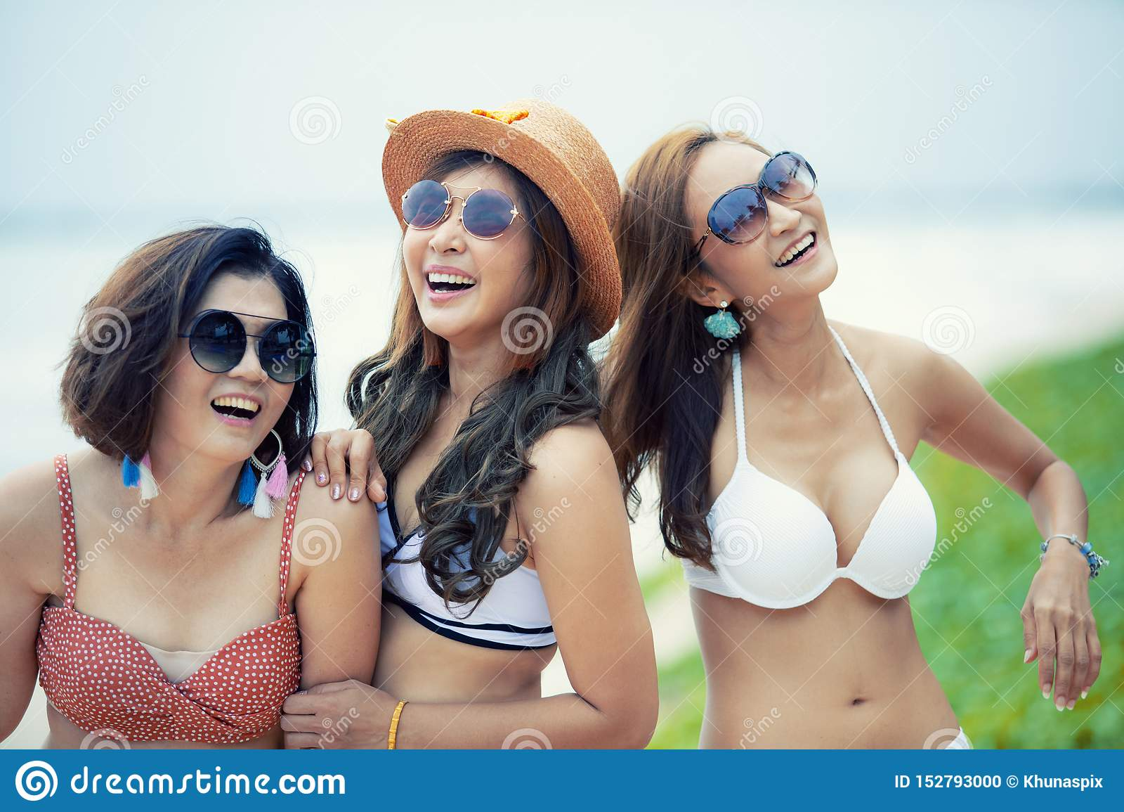 Grupo de bikini alegre de la playa de una mujer más joven del asiático que lleva que ríe con la emoción de la felicidad