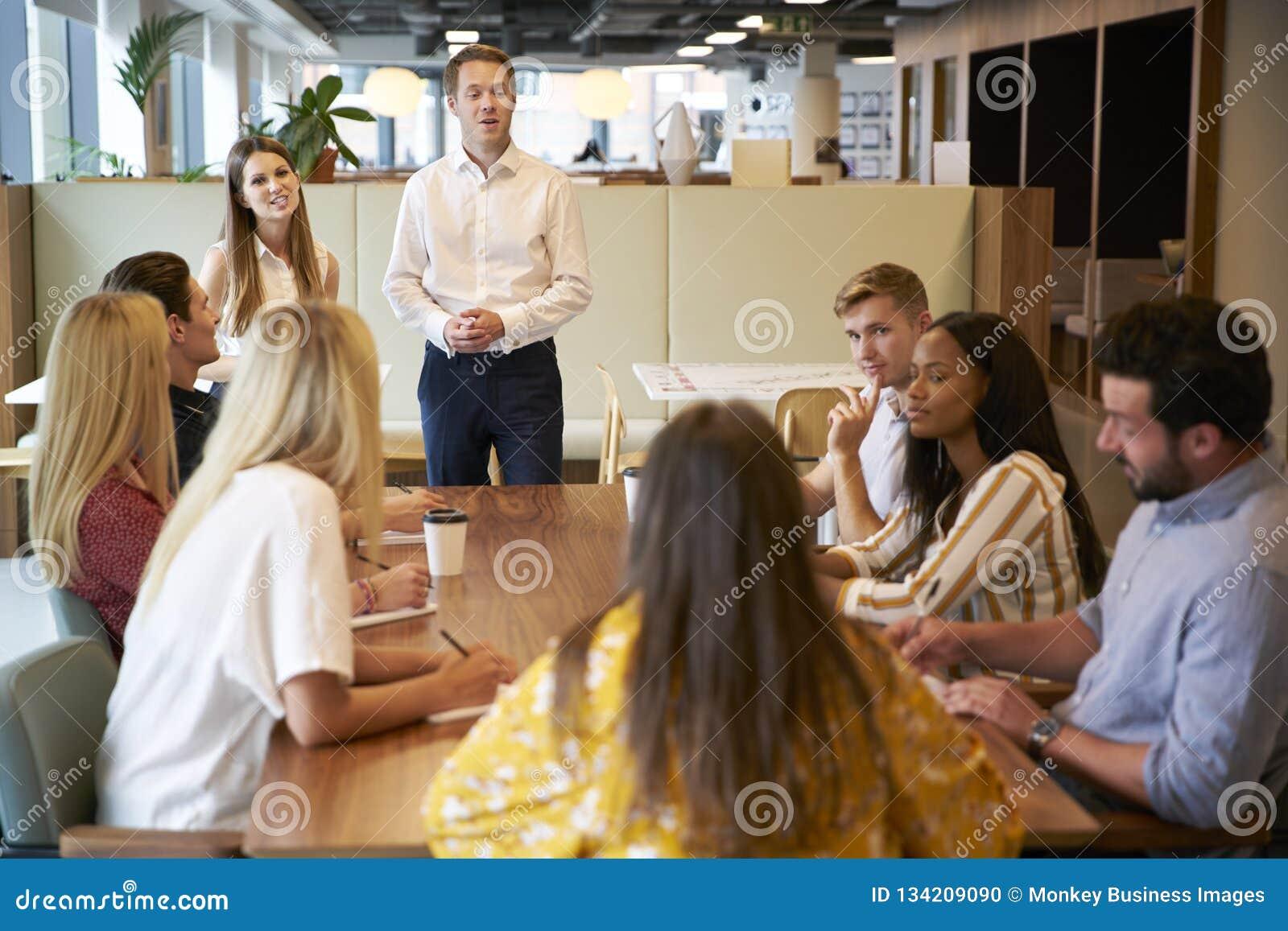 Grupo de And Businesswoman Addressing do homem de negócios de candidatos novos que sentam-se em torno da tabela