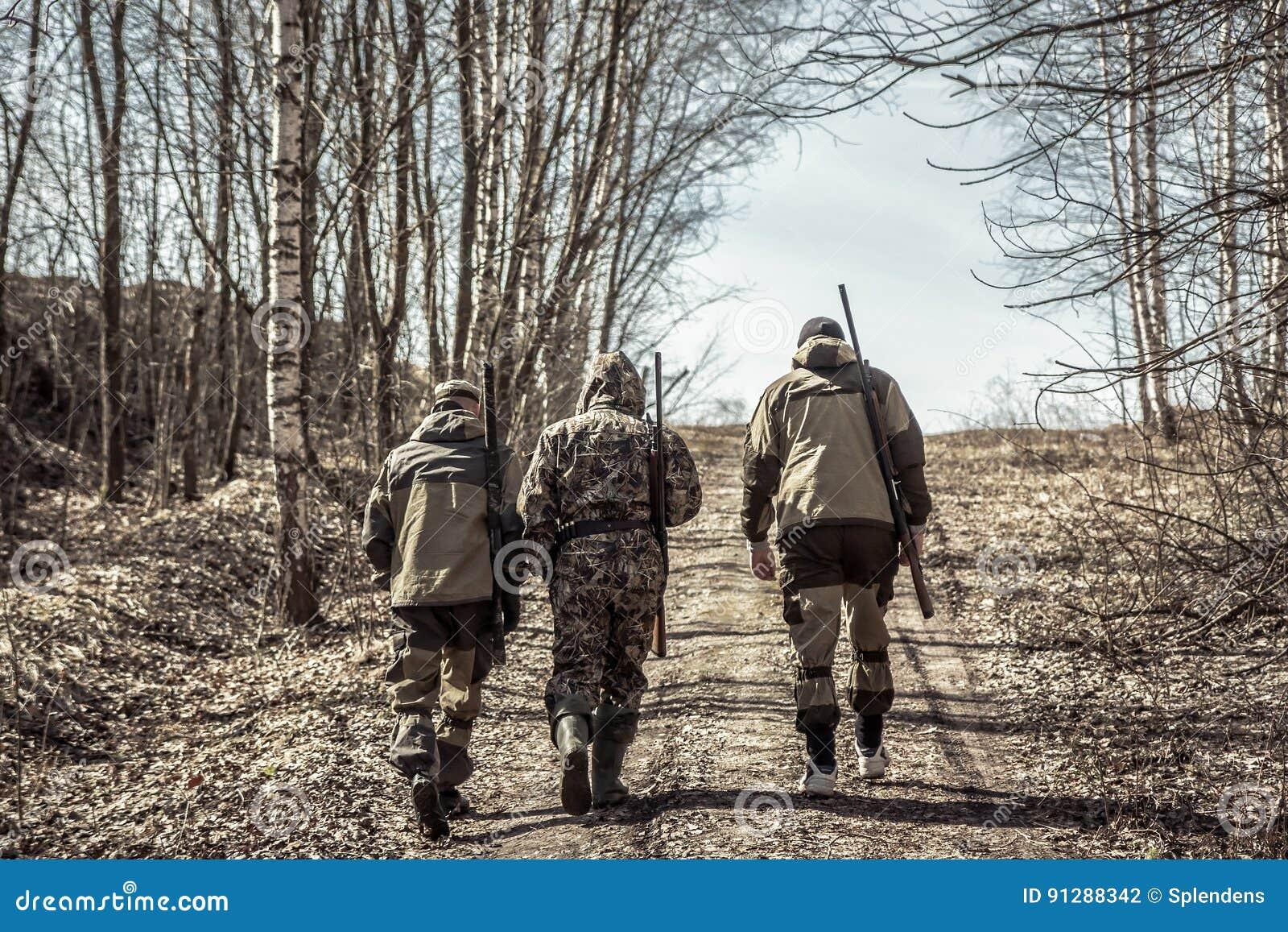 Grupo de caçadores dos homens que vão acima na estrada rural durante a época de caça