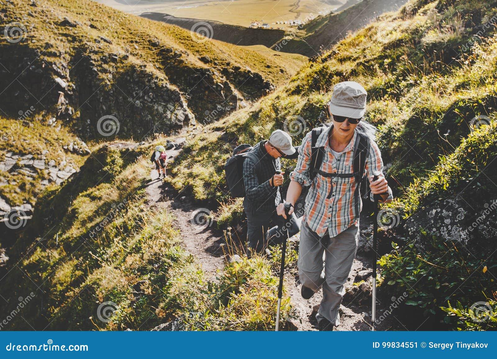 Grupo de caminantes que caminan adelante en las montañas del verano, concepto del viaje del viaje del viaje