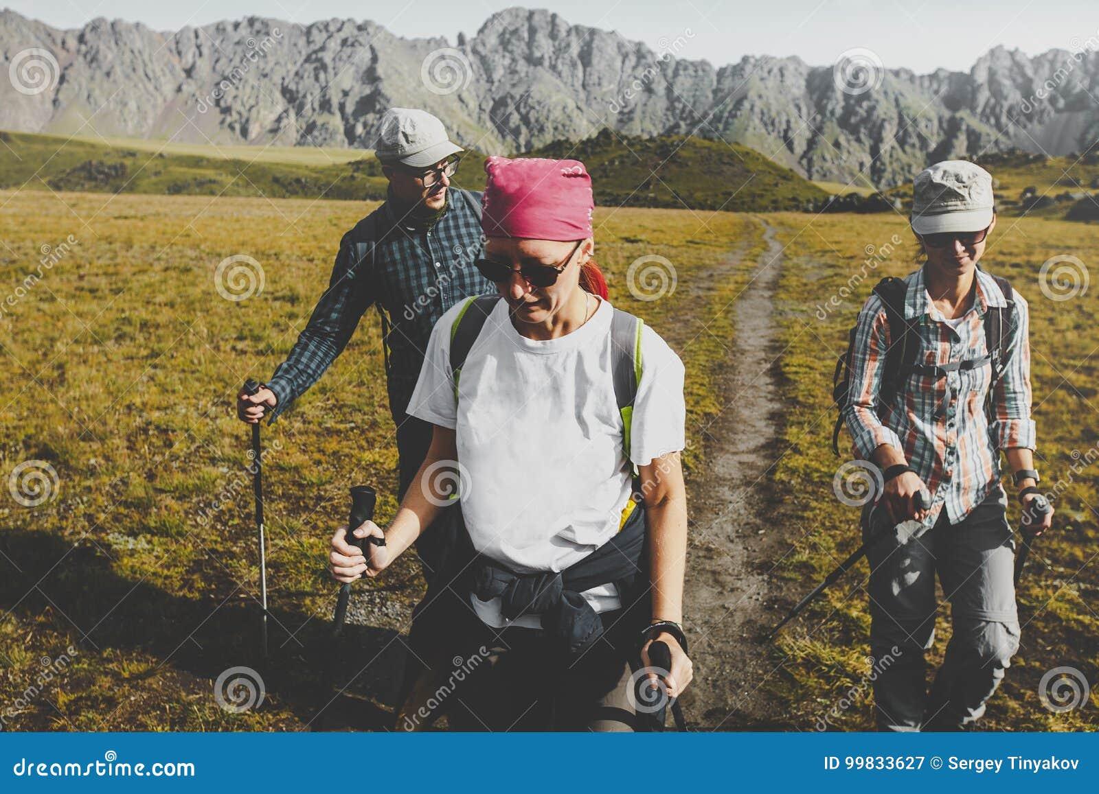 Grupo de caminantes que caminan a lo largo del llano en montañas del verano, concepto del viaje del viaje del viaje
