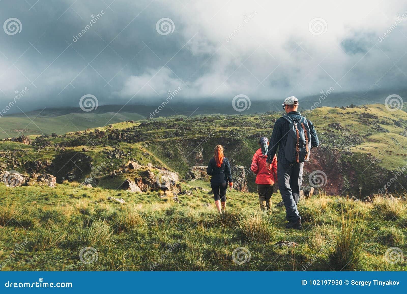 Grupo de caminantes que caminan a lo largo de las colinas verdes, vista posterior Concepto del descubrimiento del turismo del via