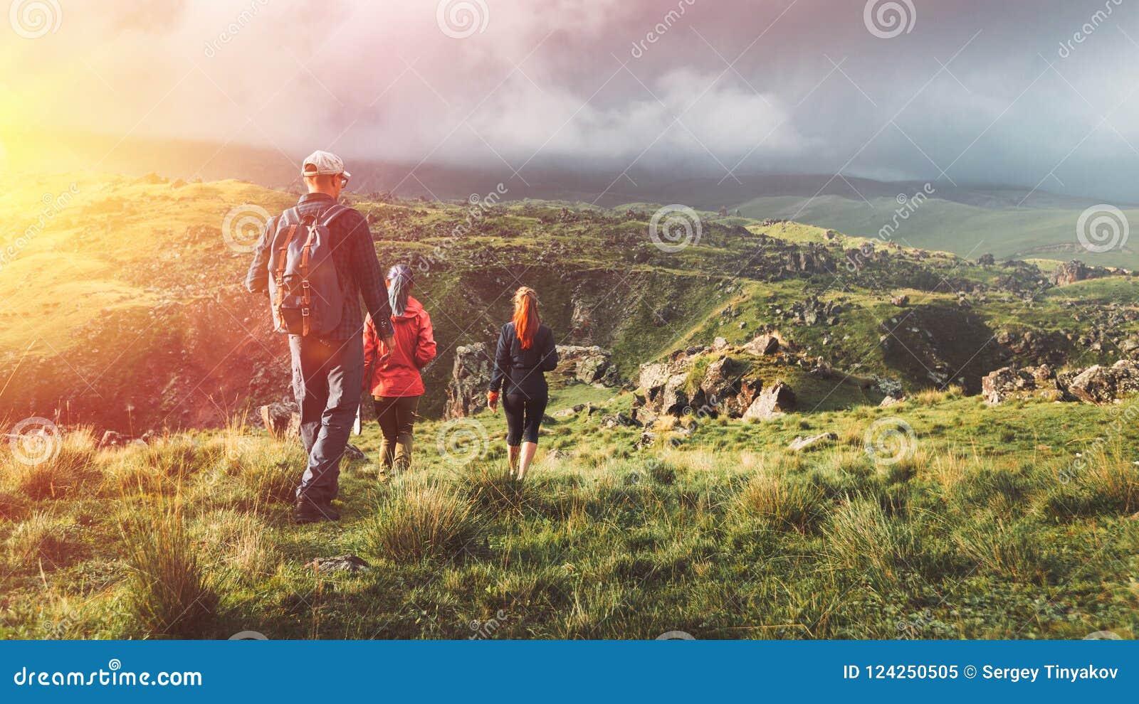 Grupo de caminantes que caminan a lo largo de las colinas verdes, vista posterior Viajes