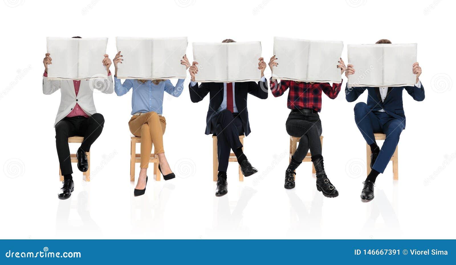 Grupo de cinco jovens que sentam e que leem jornais