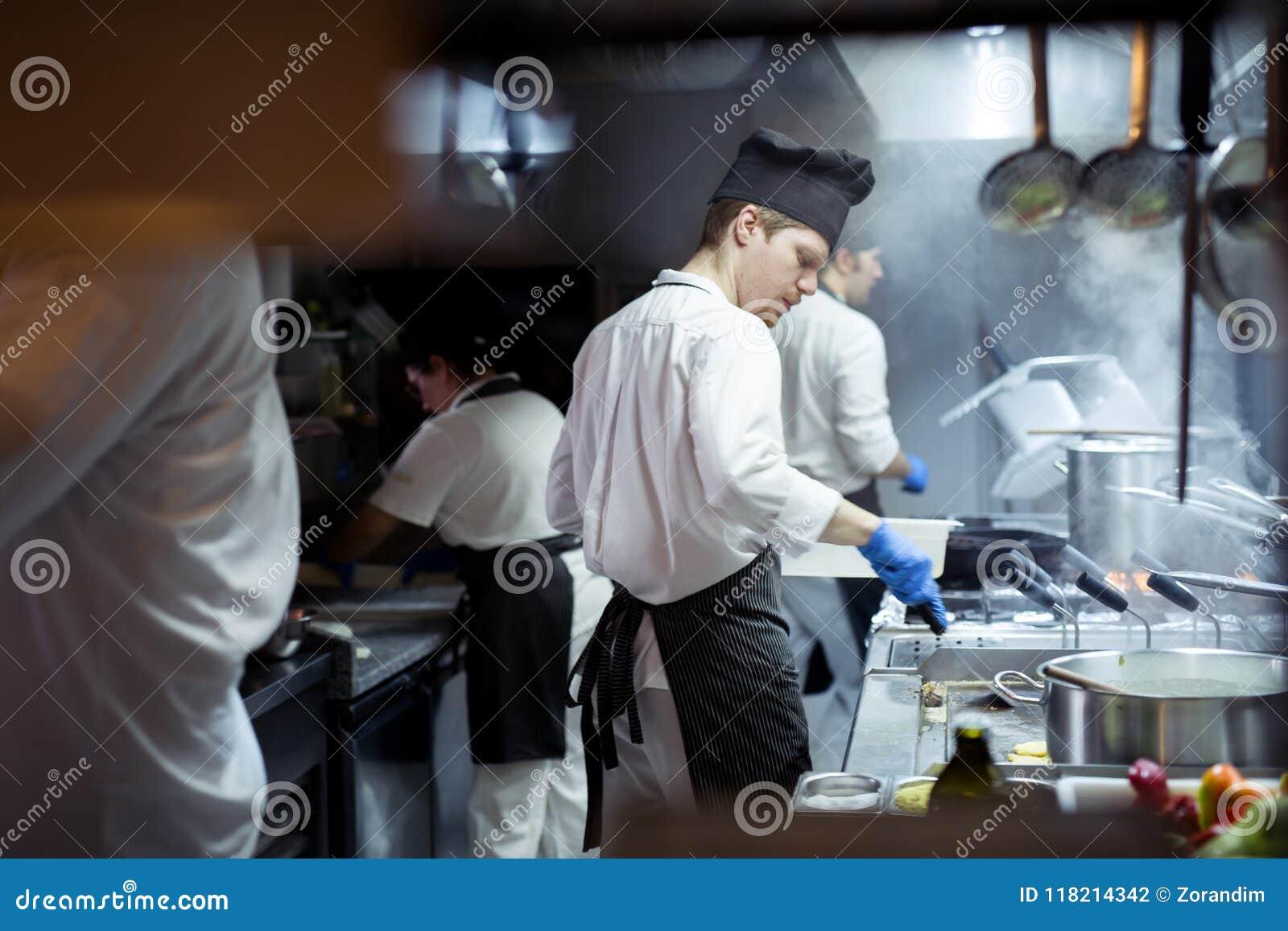 Grupo de cocinero que prepara la comida en la cocina de un restaurante