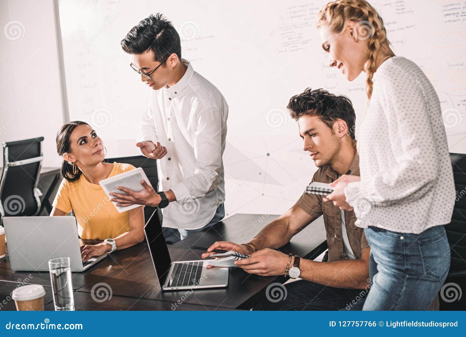Grupo de colegas multiétnicos del negocio que tienen reunión con los ordenadores portátiles y la tableta digital en moderno