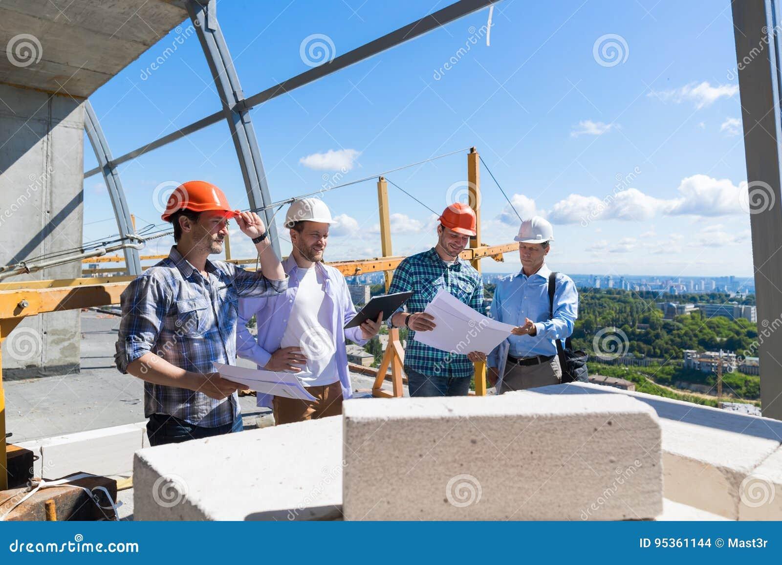 Grupo de construtores no canteiro de obras que constrói o plano do projeto da revisão do contratante de Team Of Apprentices Meeti