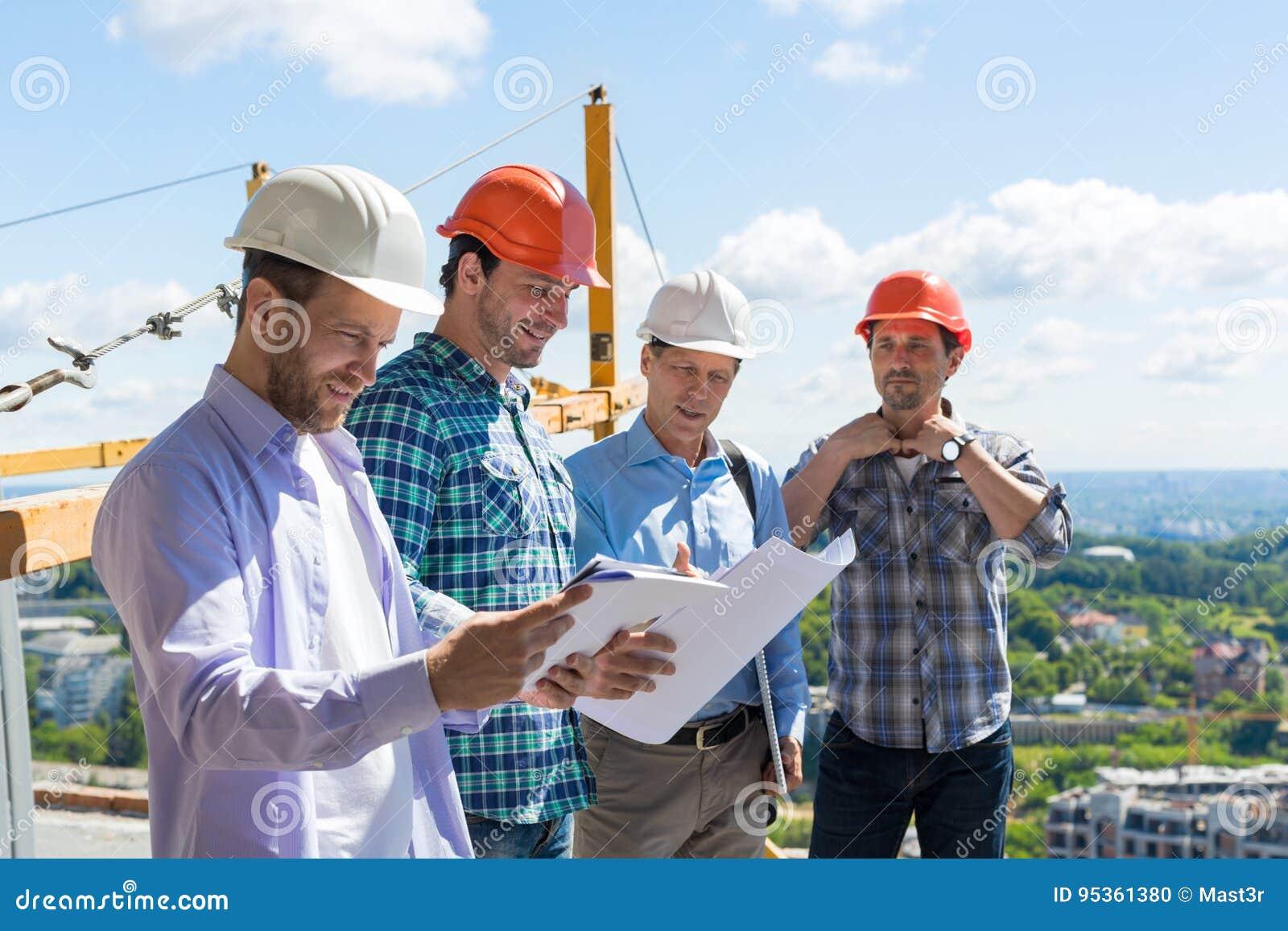 Grupo de construtores nos capacete de segurança que encontram-se no canteiro de obras que constrói trabalhos de equipa de Team Wo