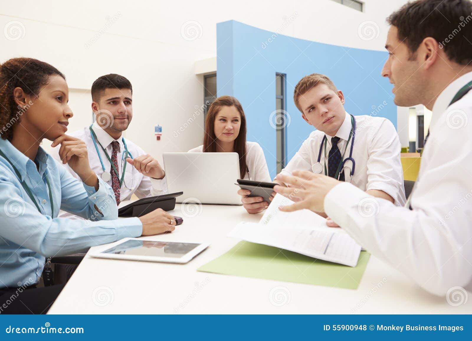 Grupo de consultantes que sentam-se na tabela na reunião do hospital
