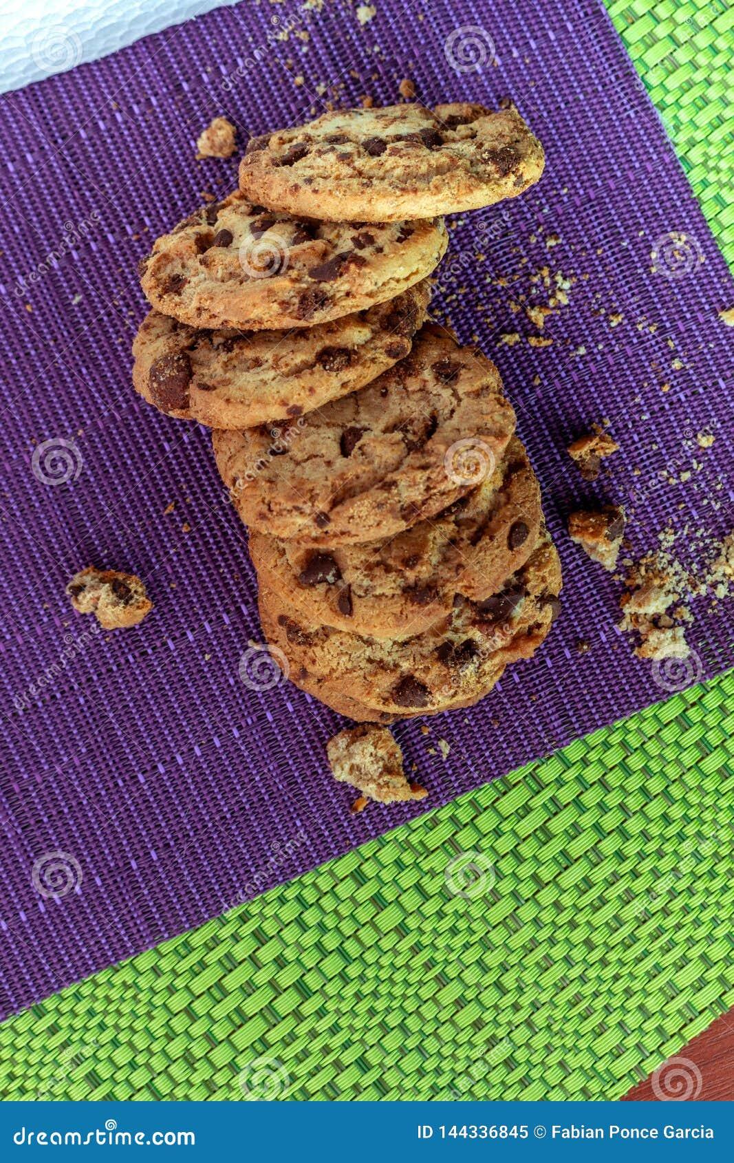Grupo de cookies declicious com as faíscas do chocolate na toalha de mesa roxa e verde com partes de galllette