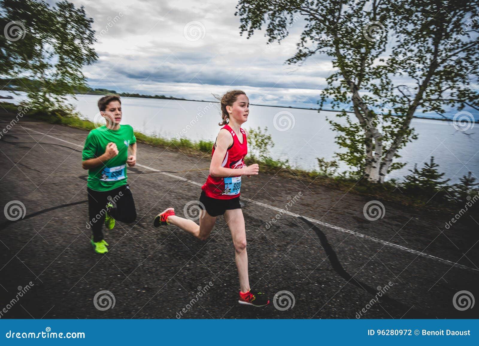 Grupo de corredores jovenes y de niños que compiten con junto