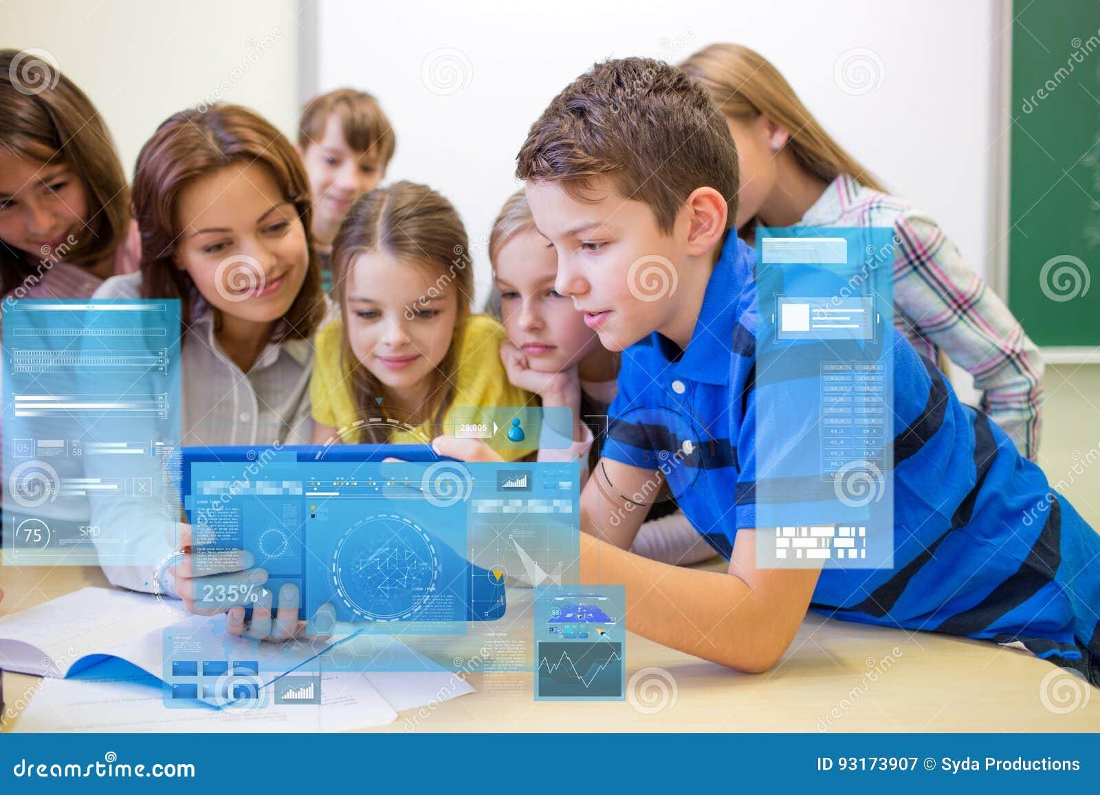 Grupo de crianças com o PC do professor e da tabuleta na escola
