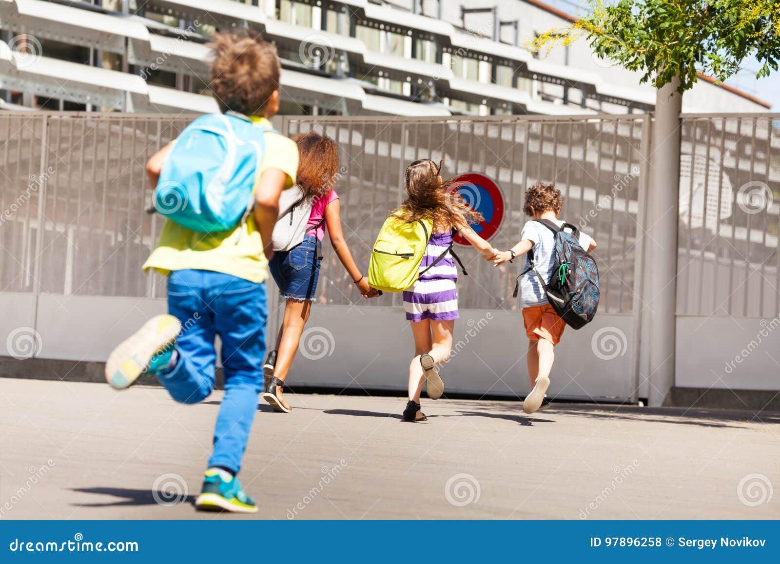 Grupo de crianças corridas à escola um após o outro