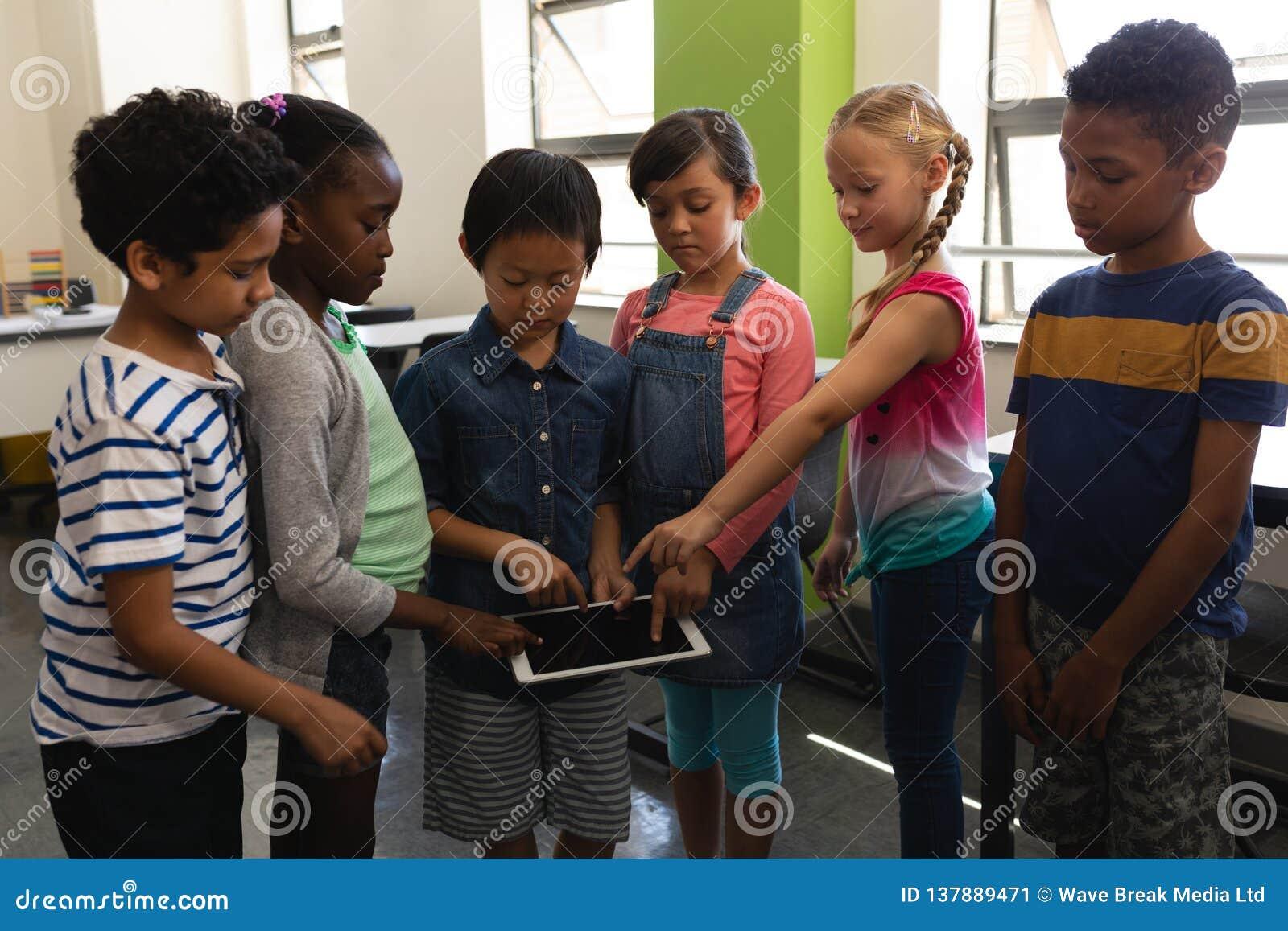 Grupo de crianças da escola que estudam junto na tabuleta digital na sala de aula