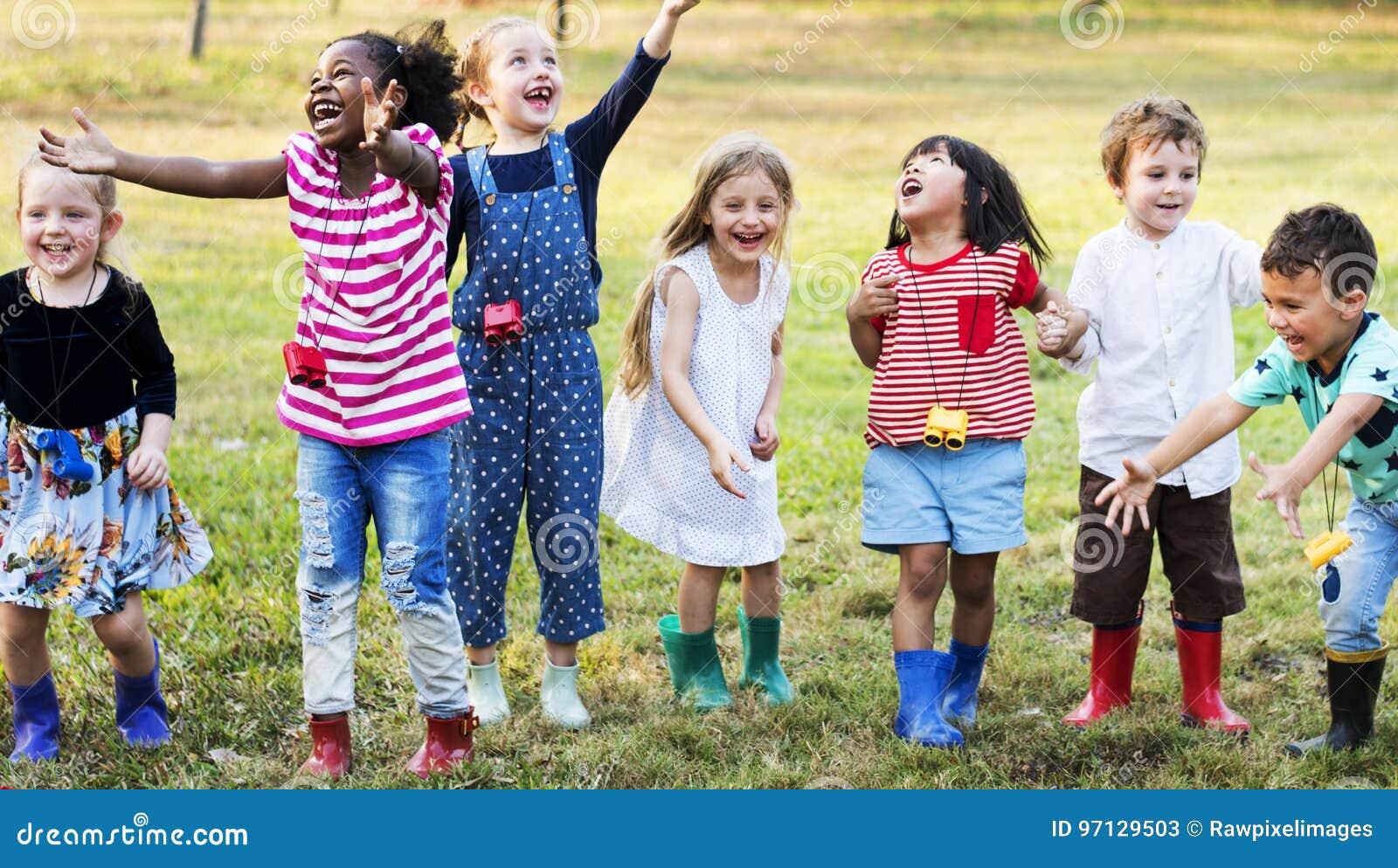Grupo de crianças do jardim de infância que aprendem a jardinagem fora campo tri