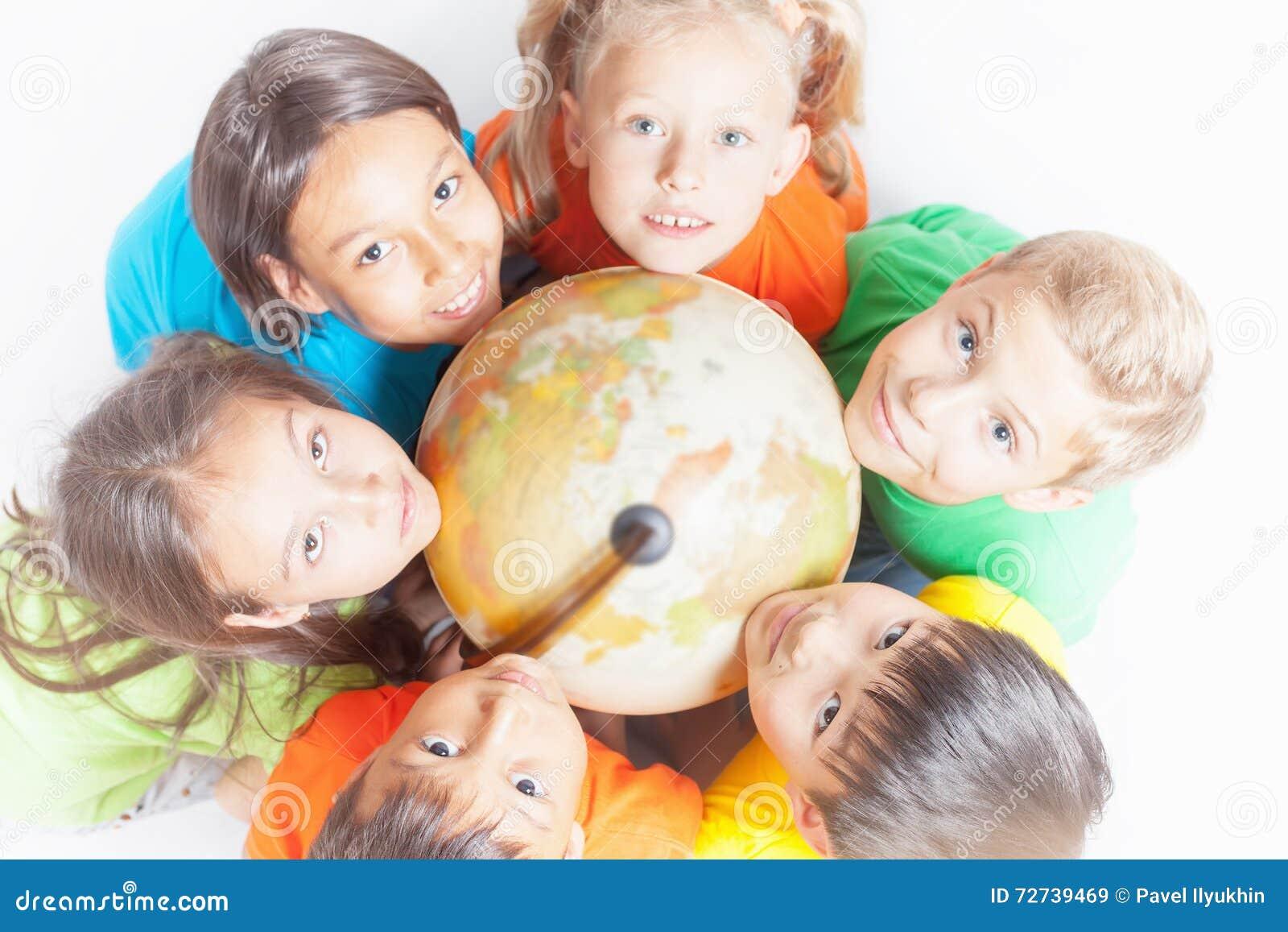 Grupo de crianças internacionais que guardam a terra do globo