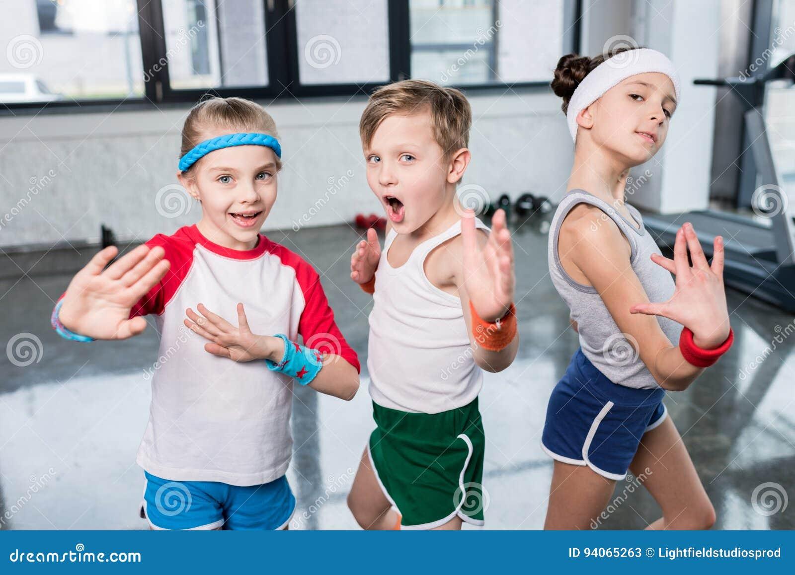Grupo de crianças no sportswear que exercitam e que levantam na câmera no gym