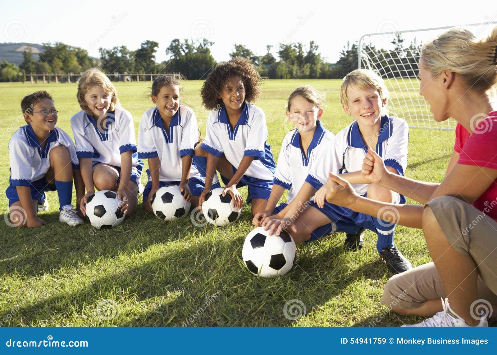 Grupo de crianças no treinador de Team Having Training With Female do futebol