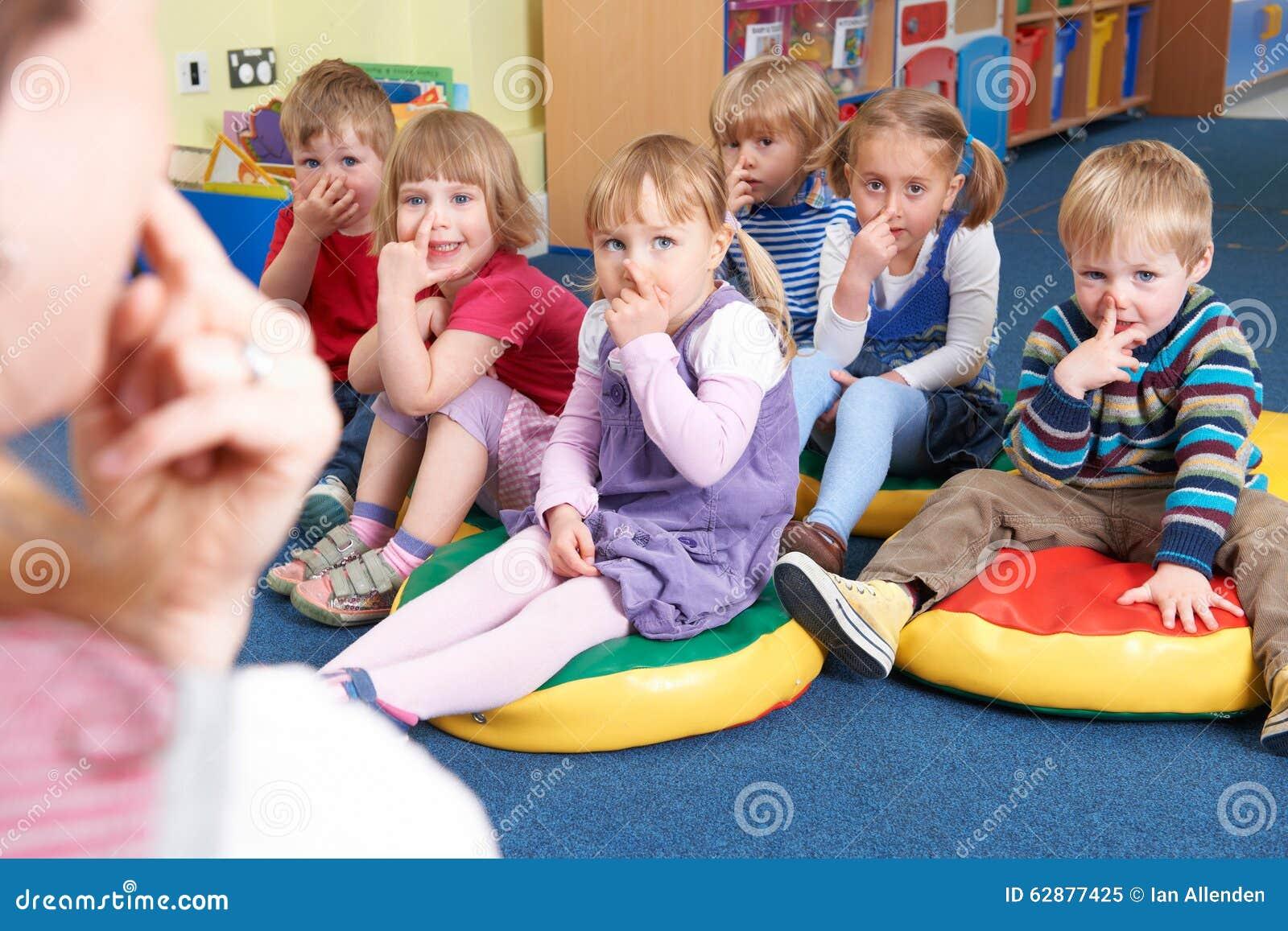 Grupo de crianças que copiam a classe de In Montessori /Pre-School do professor