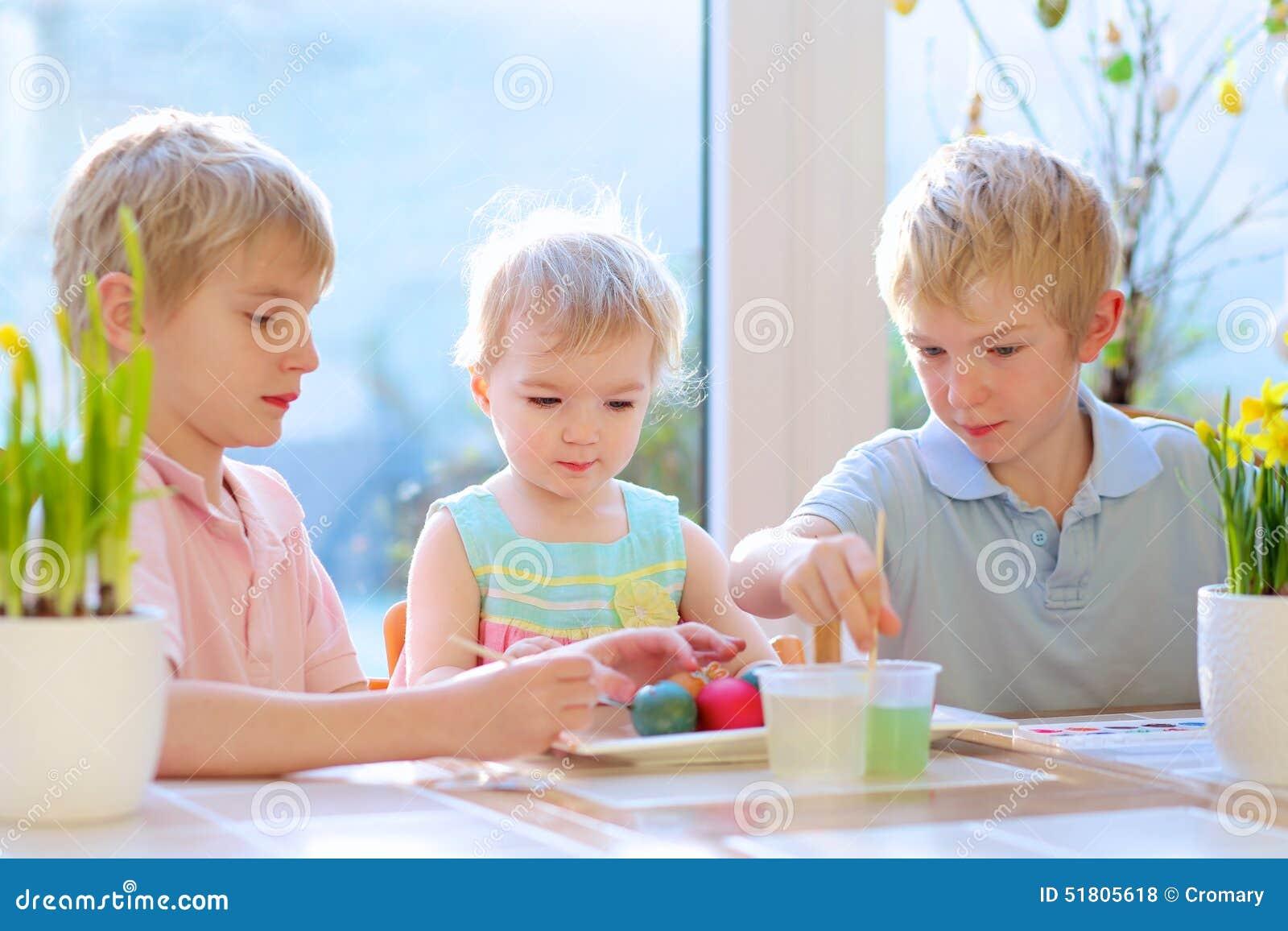 Grupo de crianças que decoram ovos da páscoa
