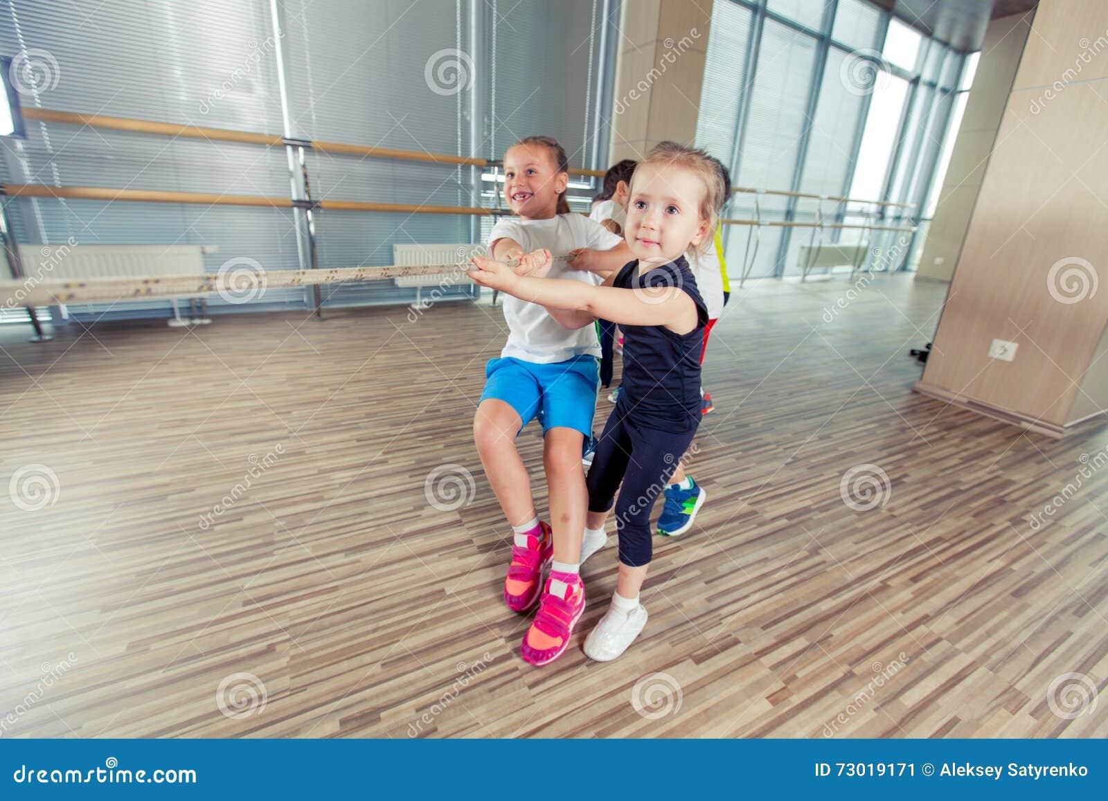 Grupo de crianças que puxam uma corda na sala da aptidão