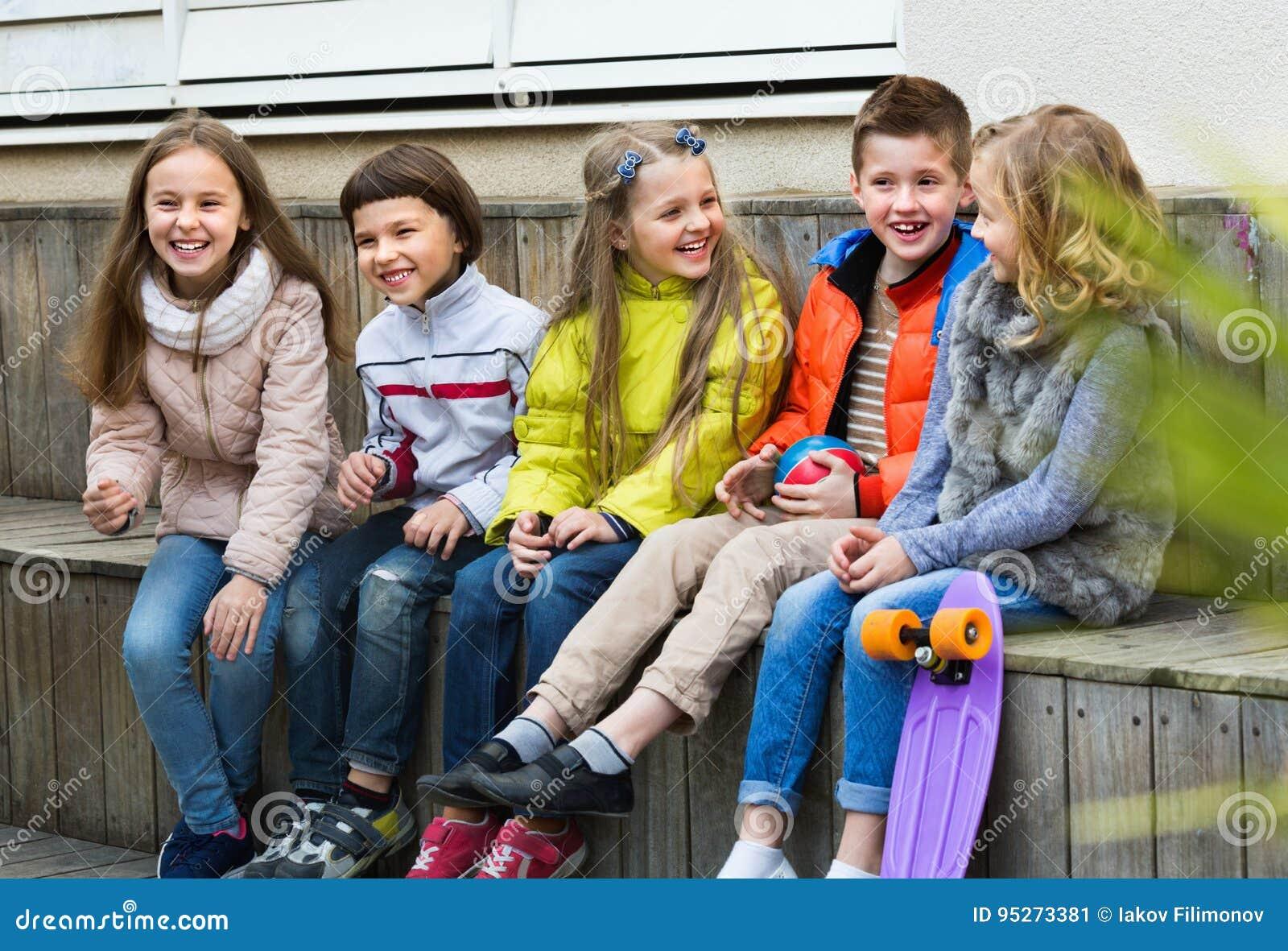 Grupo de crianças que sentam-se no banco