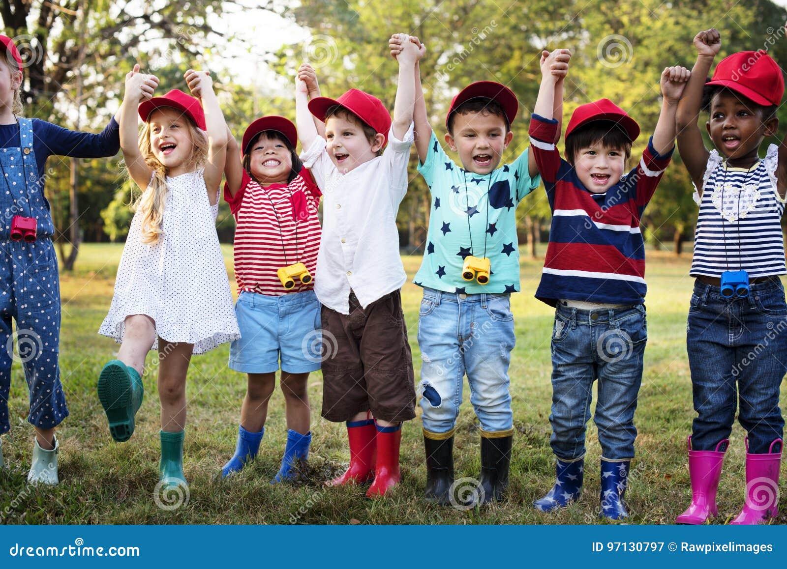Grupo de disparos al campo de la escuela de los niños que aprende al aire libre el parque botánico
