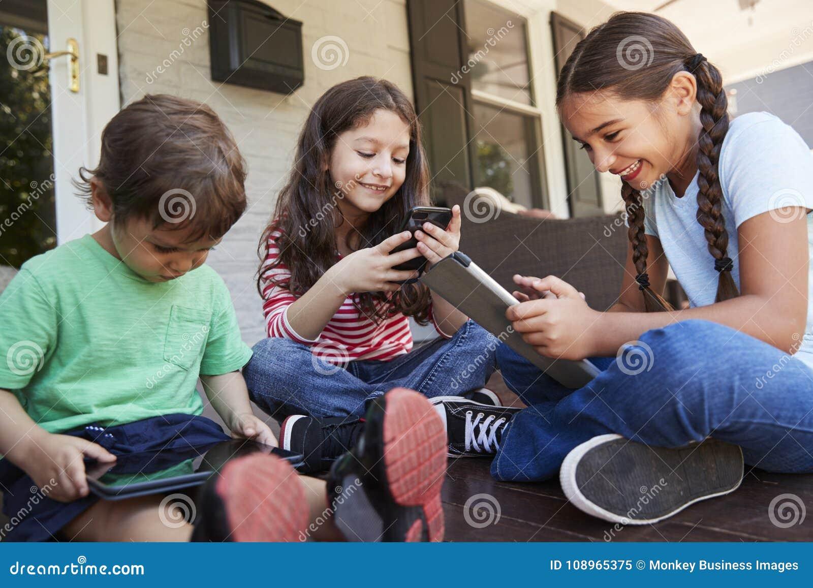 Grupo de dispositivos de Sit On Porch Playing With Digital das crianças