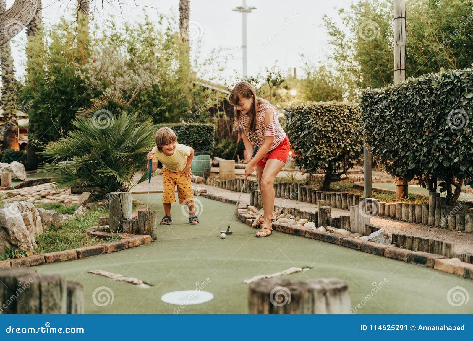 Grupo de duas crianças engraçadas que jogam o mini golfe