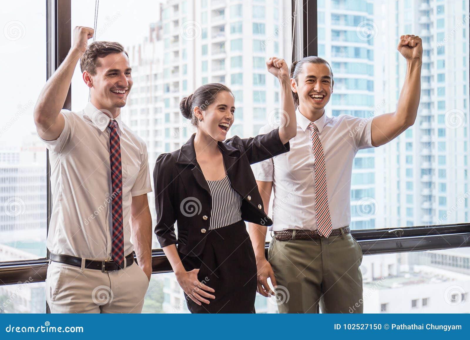 Grupo de empregados com suas mãos que mantêm unido e que têm o divertimento na reunião de negócios