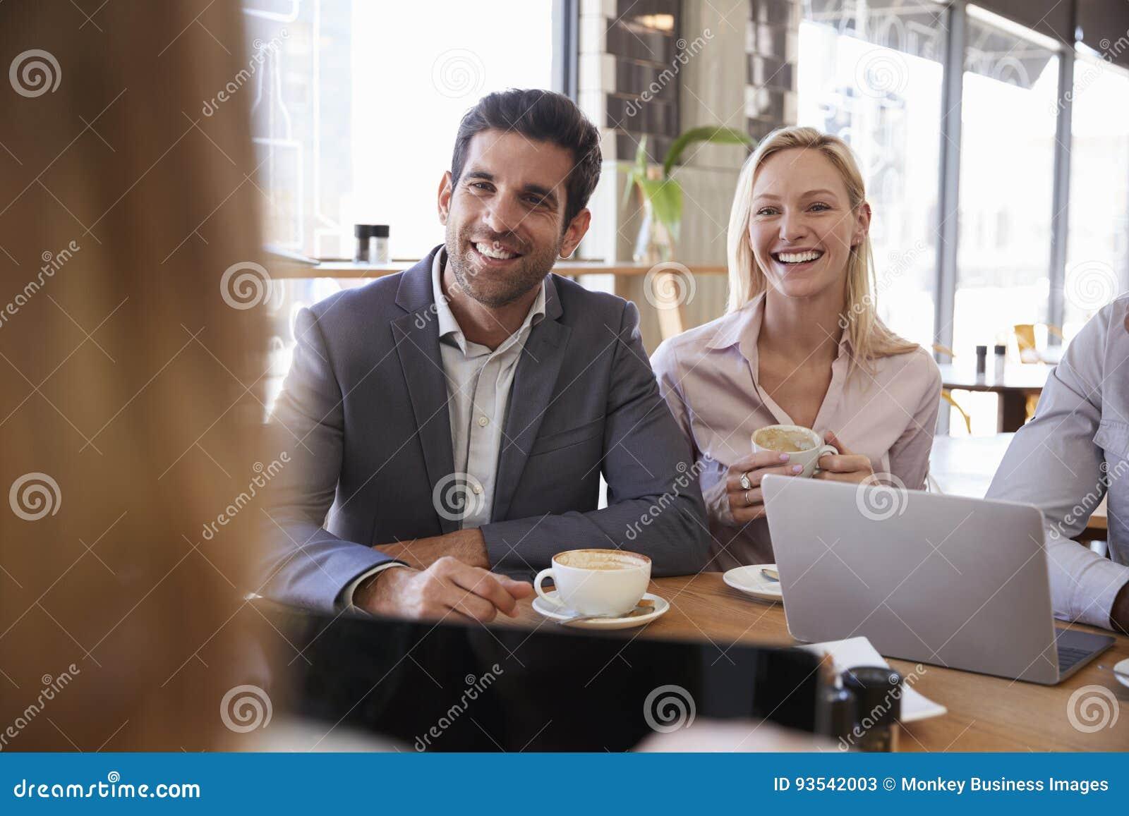 Grupo de empresários que têm a reunião na cafetaria