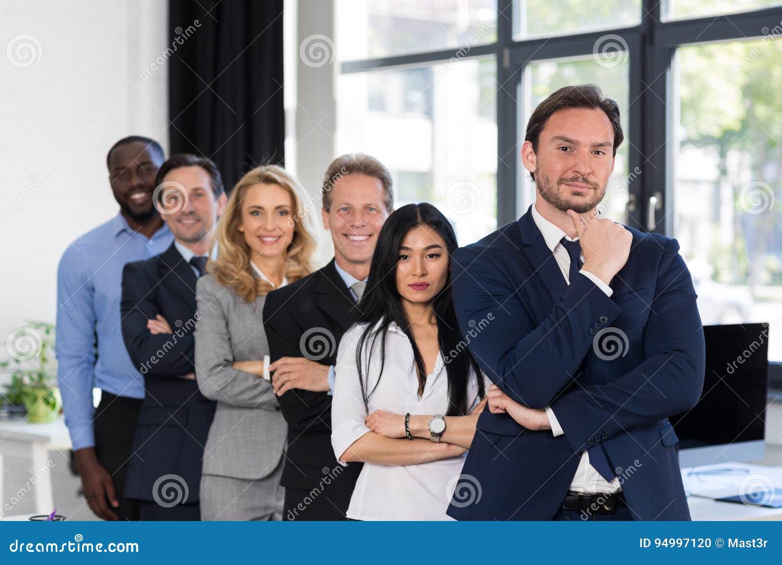 Grupo de empresarios en oficina creativa con el líder de sexo masculino On Foreground Businessmen y el equipo acertado de las emp