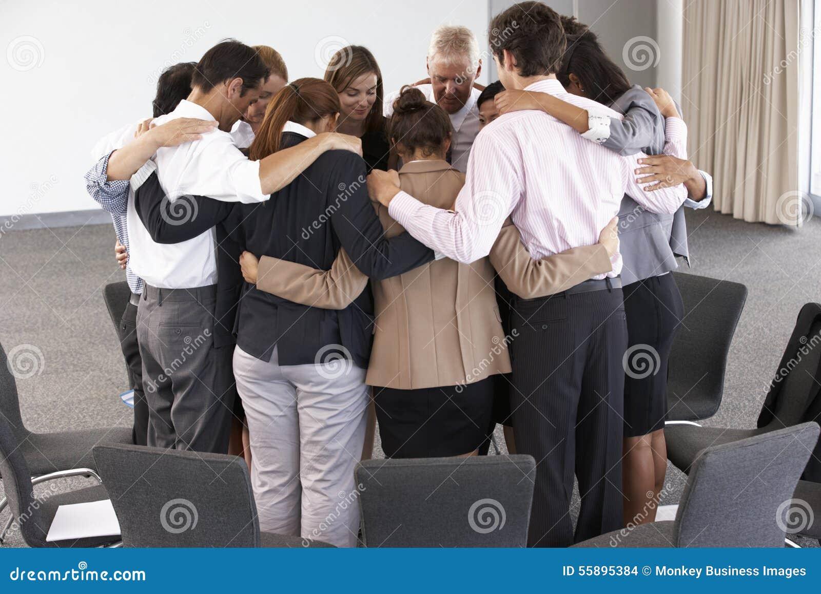 Grupo de empresarios que enlazan en círculo en el seminario de la compañía