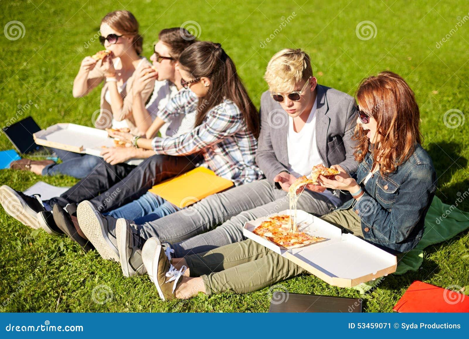 Grupo de estudantes adolescentes que comem a pizza na grama