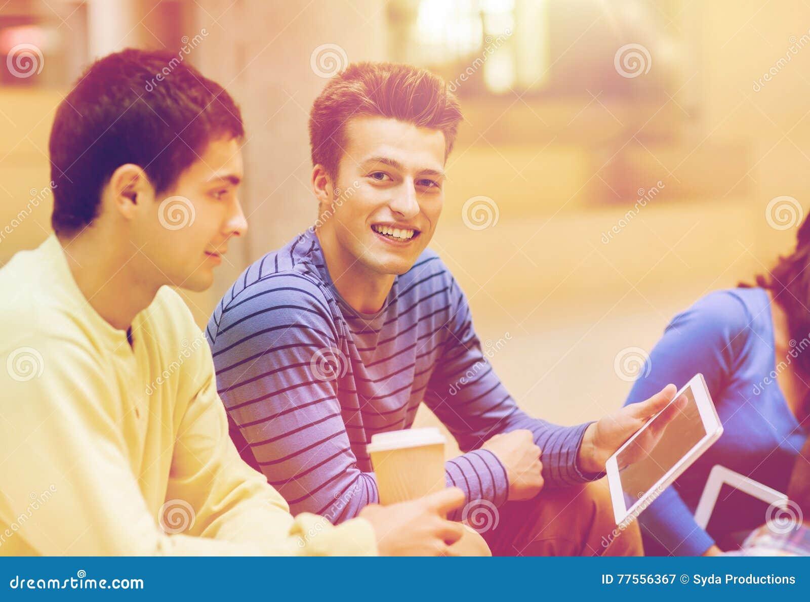 Grupo de estudantes com PC da tabuleta e copo de café