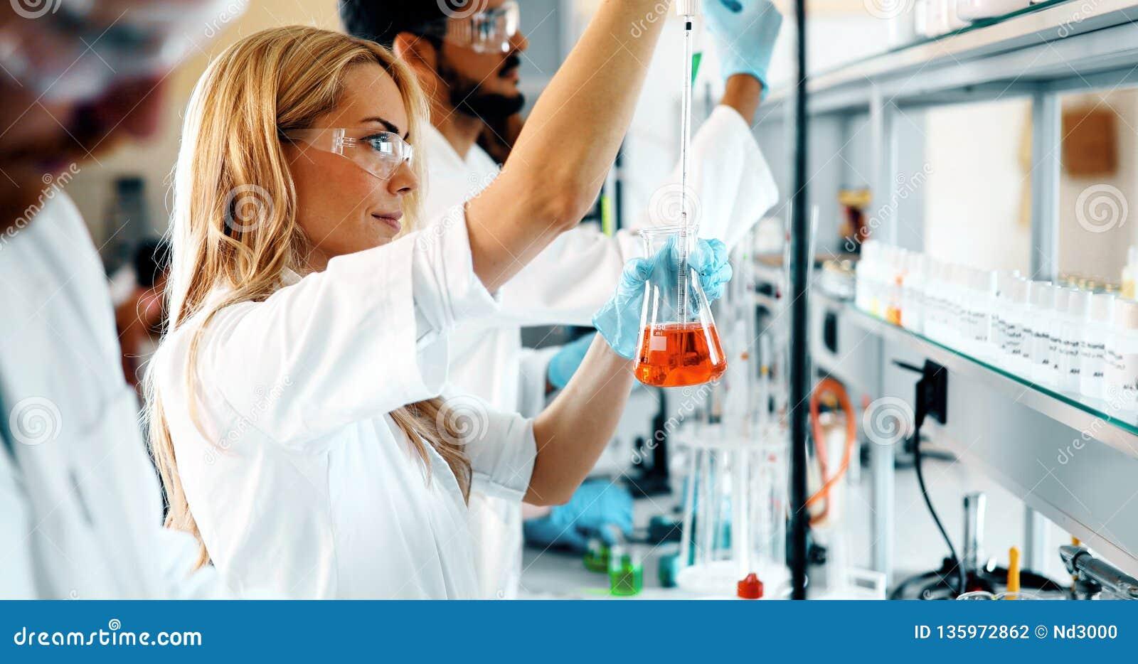 Grupo de estudantes da química que trabalham no laboratório