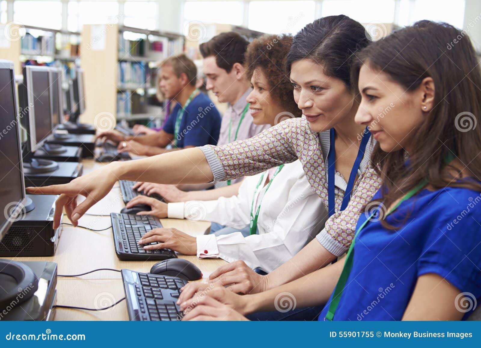 Grupo de estudantes maduros que trabalham em computadores com tutor