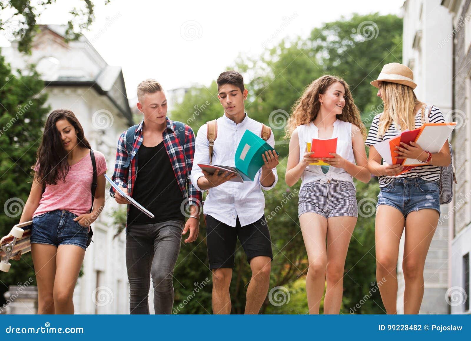 Grupo de estudiantes adolescentes atractivos que caminan a la universidad