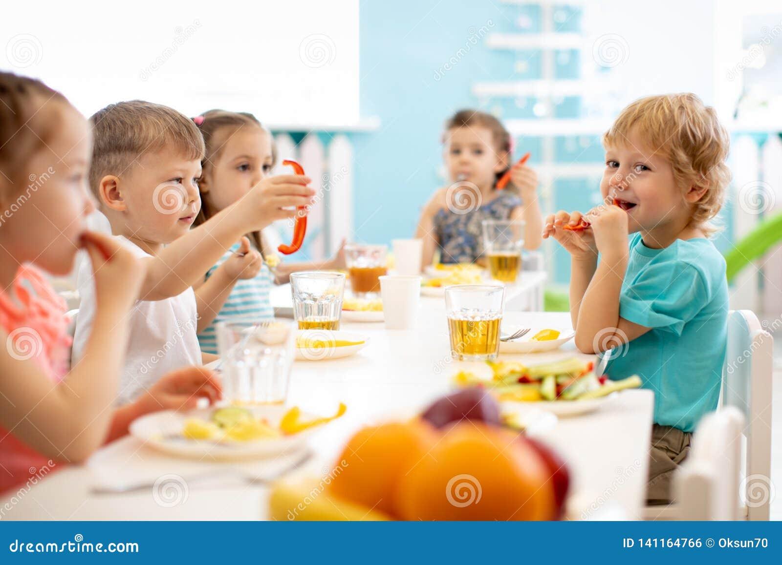 Grupo de estudiantes de la guardería que comen la hora de la almuerzo sana de la comida junto
