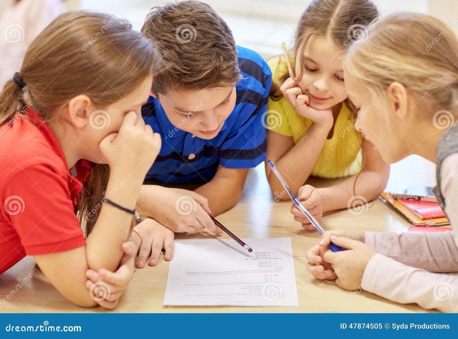 Grupo de estudiantes que hablan y que escriben en la escuela