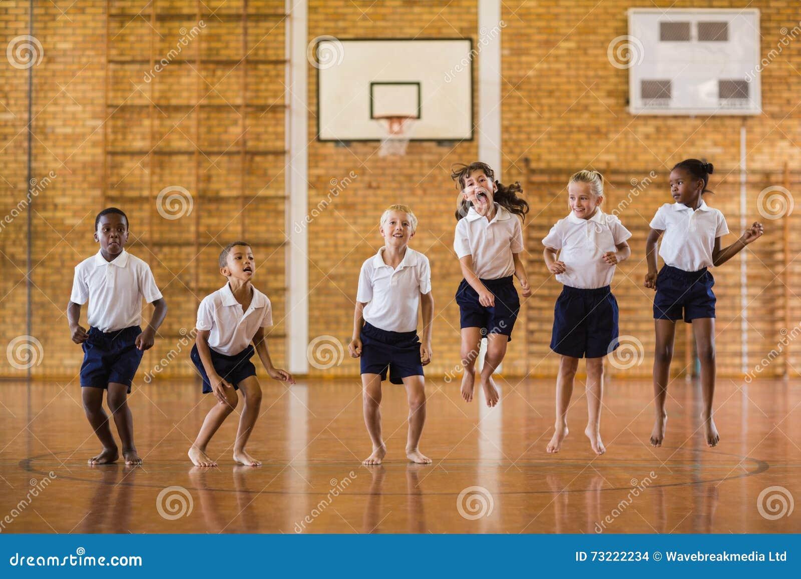 Grupo de estudiantes que saltan en gimnasio de la escuela