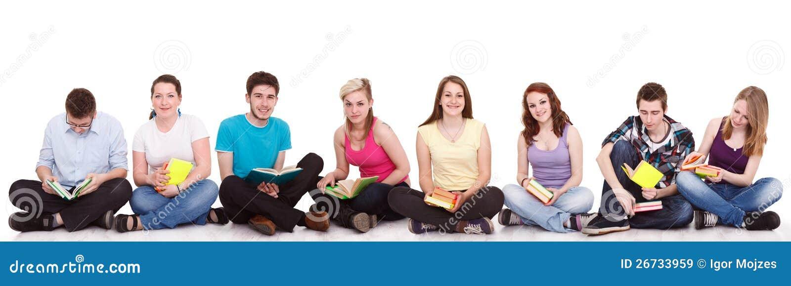 Grupo de estudiantes que se sientan en el suelo