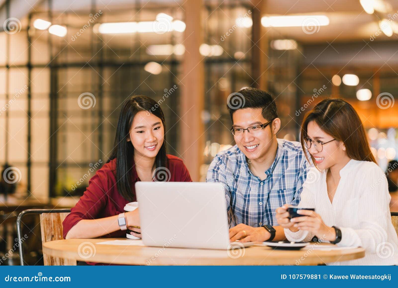 Grupo de estudiantes universitarios o compañeros de trabajo asiáticos que usan el ordenador portátil junto en el café o la univer