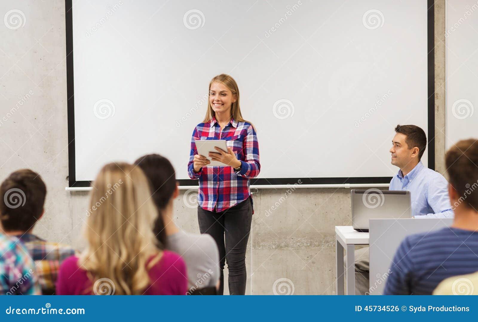 Grupo de estudiantes y de profesor sonrientes en sala de clase