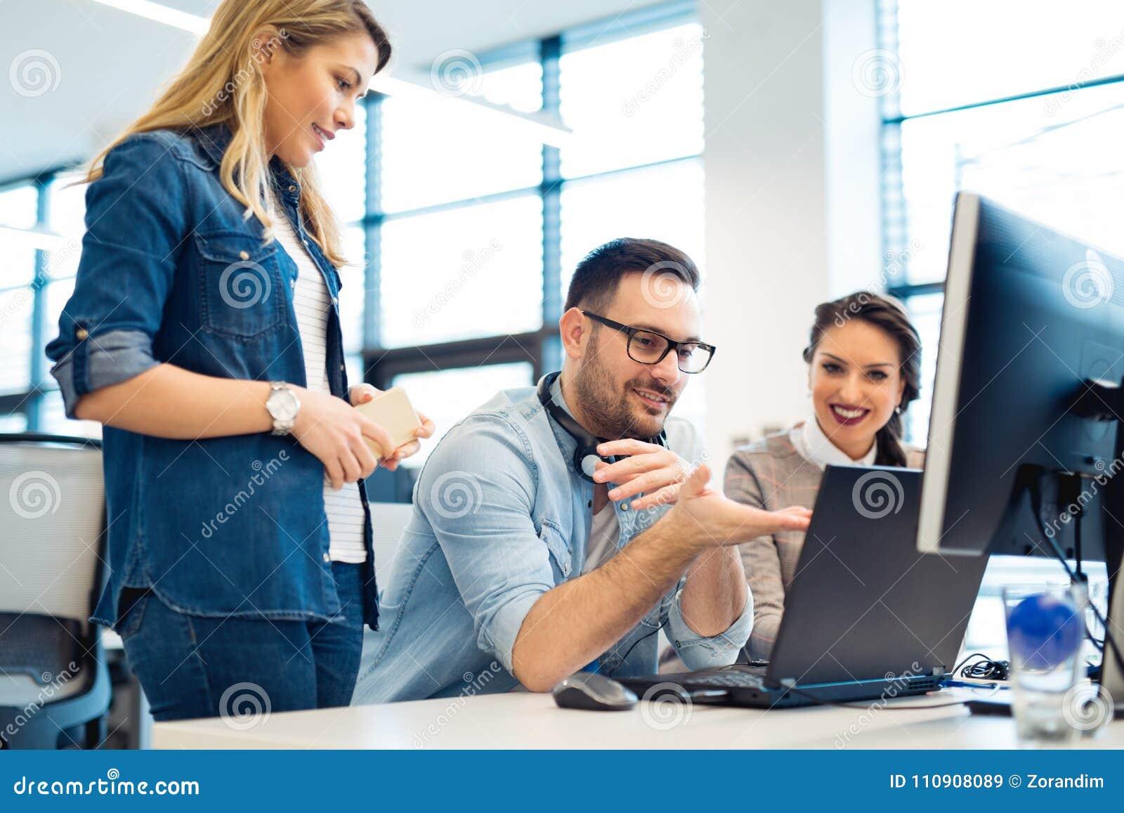Grupo de executivos e de programadores de software que trabalham em equipe no escritório